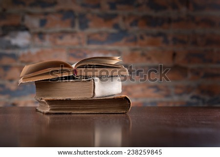 Vintage old and new books on a wooden table top  against a brick wall - stock photo