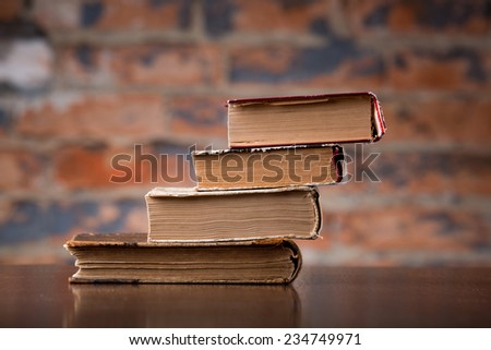 Vintage old books on a wooden table top  against a brick wall - stock photo