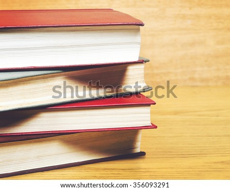 Vintage old books on yellow wooden deck tabletop against brown grunge wall  - stock photo