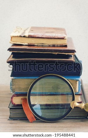 vintage old books stacked on table with finding glass - stock photo
