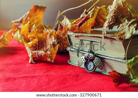 Vintage old books with bronze clock in form of owl between pages on the red linen tablecloth among the dry yellow maple leaves.  Selective focus at the clock - shallow depth of field - stock photo