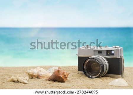 Vintage old camera and shells on sandy beach. Travel concept background. - stock photo