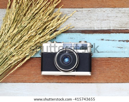 Vintage old camera with flower on the wooden.  - stock photo