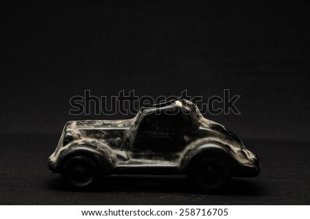 Vintage Old Ceramic Black Car on the Dark background - stock photo