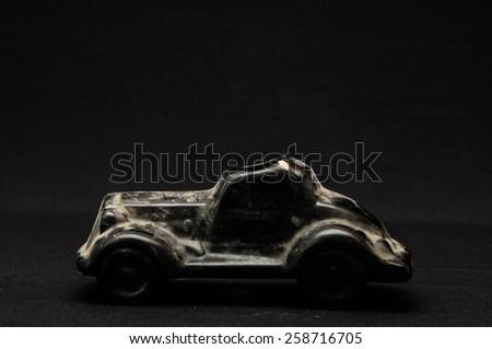 Vintage Old Ceramic Black Car on the Dark background - stock photo