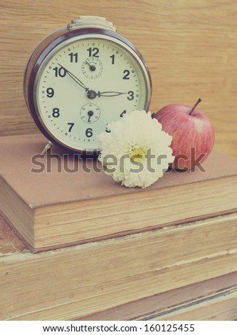 Vintage old clock and flower on books - stock photo