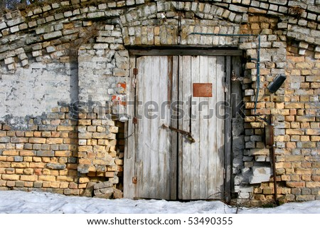 Vintage old door with brick wall. Front view of the entrace to abonded warehouse on the main street in center of Riga, Latvia. - stock photo