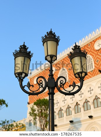 Vintage Old Fashioned Street Light against mansion in blue sky  - stock photo