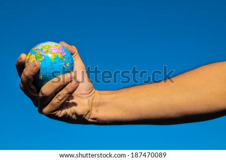 Vintage Old Globe Earth and Human Hand over a Blue Sky
