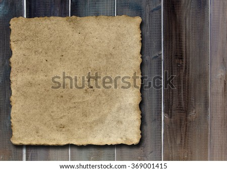 Vintage old grungy paper banner over ancient wood texture background metaphor for aged, retro, wooden, dirty, textured, manuscript, antique, parchment, book, ancient, weathered or grungy - stock photo