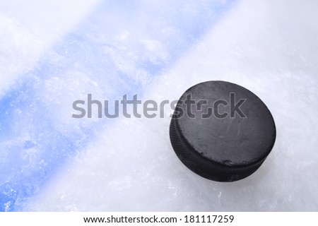 Vintage old hockey puck is on the ice near the blue line - stock photo