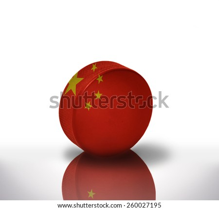 vintage old hockey puck with the chinese flag - stock photo