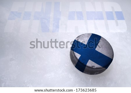 Vintage old hockey puck with the Finland flag is on the ice - stock photo