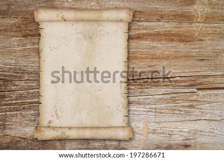 vintage old paper scroll on wooden table - stock photo