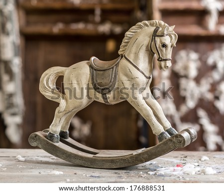 Vintage old rocking horse on a wooden background - stock photo
