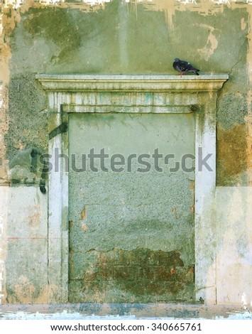 Vintage old stone door with bird - stock photo