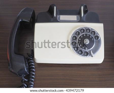 Vintage old telephone on wood table - stock photo