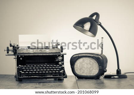Vintage old type writer, radio and retro desk lamp on wood table - stock photo