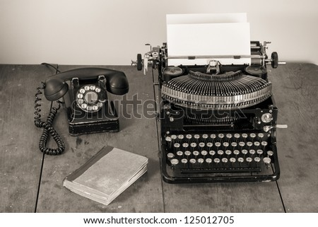 Vintage old typewriter, phone, book on table desaturated photo - stock photo