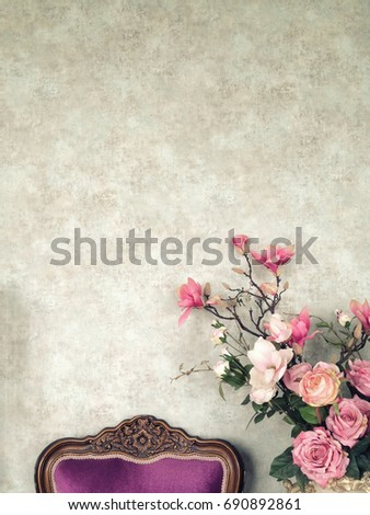 Vintage old wall background with grain texture decorated with pink flowers and roses together with dark purple antique chair with copy space for text decoration and insertion