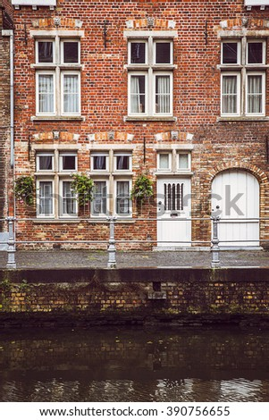 Vintage old wall with door and windows at water canal. Typical architecture of Bruges, Belgium. Image used vintage tone filter - stock photo