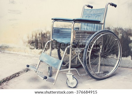 Vintage,Old Wheelchairs with wall background - stock photo