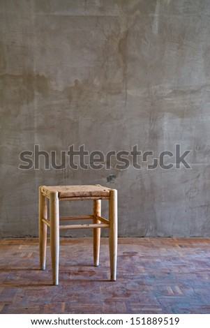 Vintage old wooden chair in grungy interior. Loneliness, estrangement, alienation concept. - stock photo