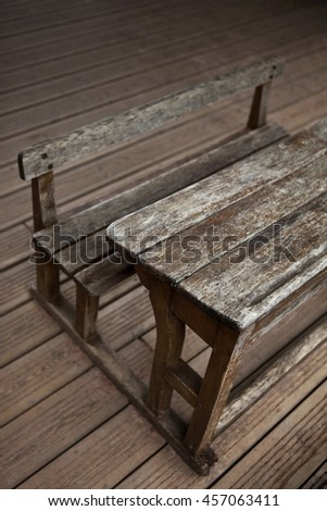 Vintage old wooden desk on floor in a classroom - stock photo