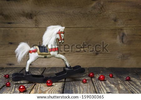 Vintage - old wooden rocking horse on a wooden old board for a christmas card with red balls - classic decoration - stock photo