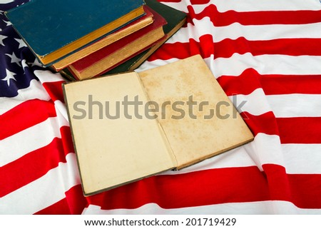 Vintage open book on American flag - stock photo
