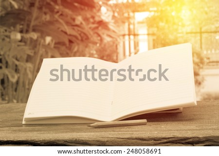 VIntage open book with pencil on grunge wood table. - stock photo