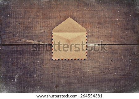 Vintage open envelope on shabby wooden background - stock photo