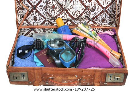 Vintage open suitcase with clothes and summer and beach  items - stock photo