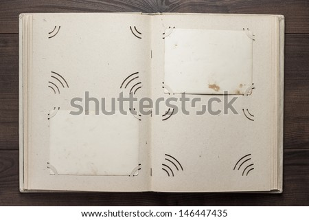 vintage opened album for photos on the wooden table - stock photo