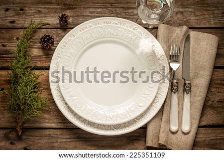 Vintage or rustic christmas table setting from above. Elegant empty white plate, cutlery on linen napkin and natural pine tree branch on rustic planked wood - country style. - stock photo