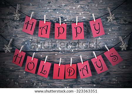 Vintage Or Shabby Chic Wooden Rustic Background. Red Tags With Happy Holidays Hanging On A Line. Snowflakes Hanging On Cloth Pegs. Christmas Card For Seasons Greetings. Frame For Night Style - stock photo