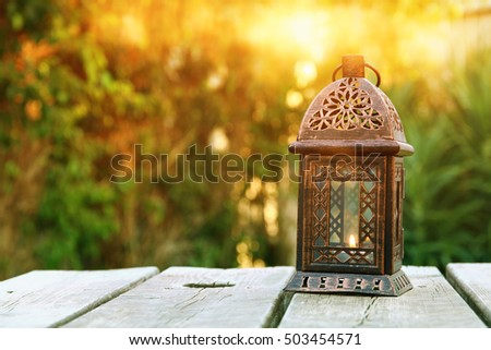 Vintage oriental lantern over wooden table outdoors in the garden at sunset light