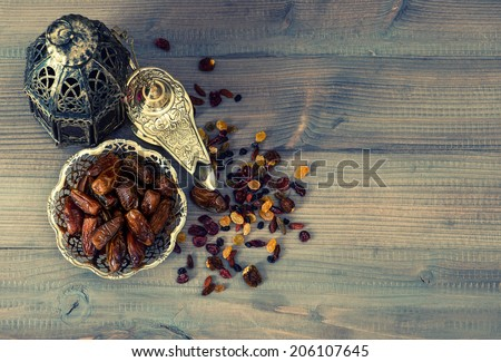 Vintage oriental lantern, raisins and dates on wooden background. retro style toned picture - stock photo