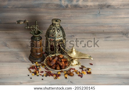 Vintage oriental latern and mill. Raisins and dates on wooden background - stock photo
