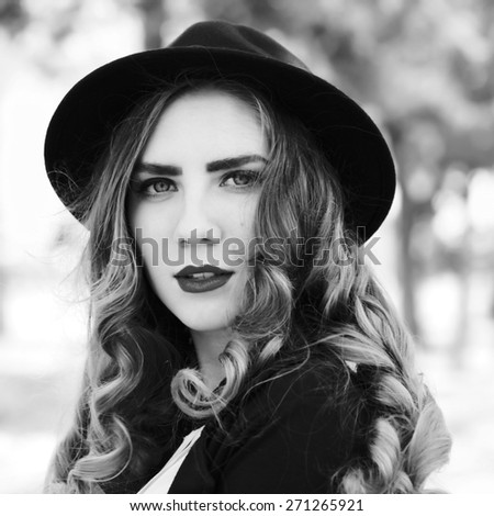 Vintage outdoor lifestyle portrait of pretty funny hipster woman. Modern urban girl having fun. Beautiful young girl in a hat. Black and white portrait, square format with a retro instagram filters.