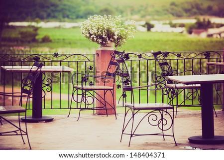 vintage outdoor restaurant focus on flowers - stock photo