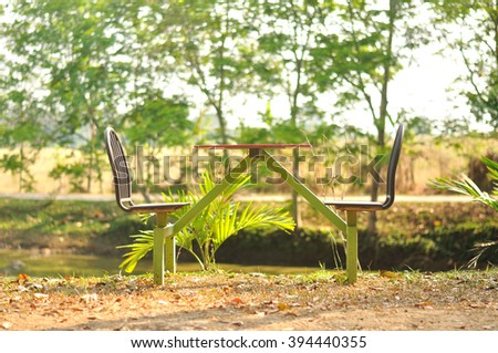 Vintage outdoor table with chairs in garden - stock photo