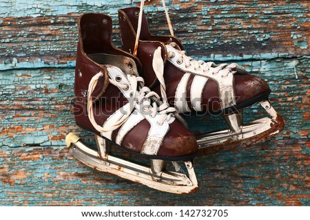 vintage pair of mens  ice skates hanging on a wooden wall - stock photo