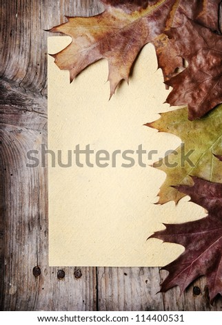 Vintage paper and autumn leaves on wooden background - stock photo