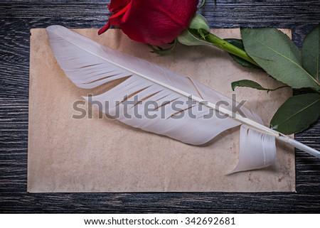 Vintage paper red rosebud feather on wooden board horizontal image.