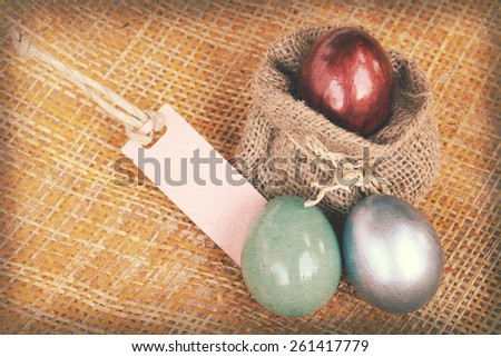 Vintage paper textures easter decoration, colorful eggs and blank tag on bamboo weave background. - stock photo