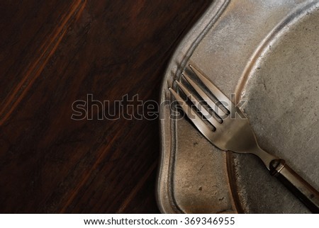 Vintage pewter fork and plate on dark rustic wood background with copy space.  Low key natural side-lighting for effect. - stock photo