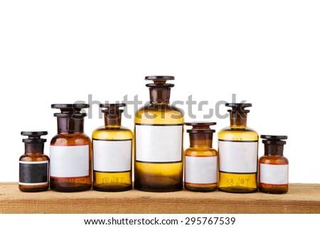 vintage pharmacy bottles on wooden board - stock photo