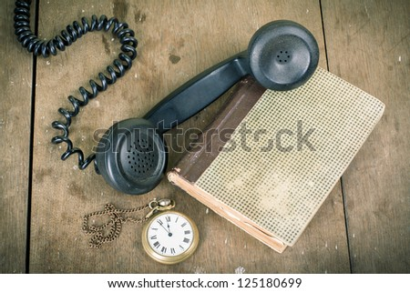 Vintage phone handset, pocket watches, old book, on wooden table grunge background - stock photo