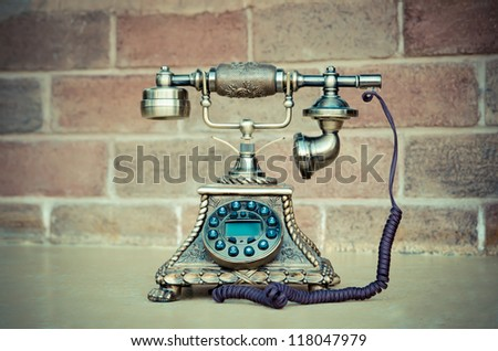 Vintage phone isolate on brick background - stock photo